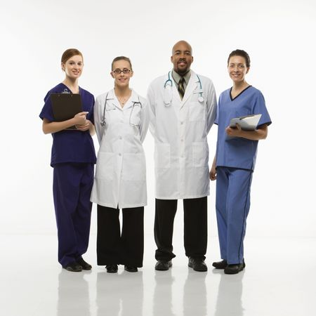 Full-length portrait of African-American man and Caucasian women medical healthcare workers smiling in uniforms standing against white background. Stock Photo