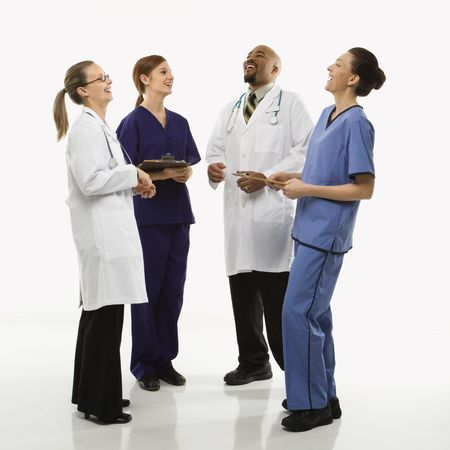 Full-length portrait of African-American man and Caucasian women medical healthcare workers in uniforms laughing standing against white background.