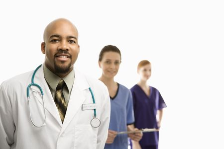 Portrait of smiling African-American man and Caucasian women medical healthcare workers in uniforms standing against white background. photo