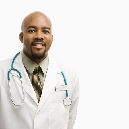 Portrait of smiling African-American man doctor wearing uniform standing against white background. photo
