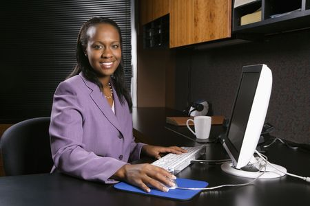 African-American young adult business woman working at computer in office smiling and looking at viewer. Stock Photo - 1796917