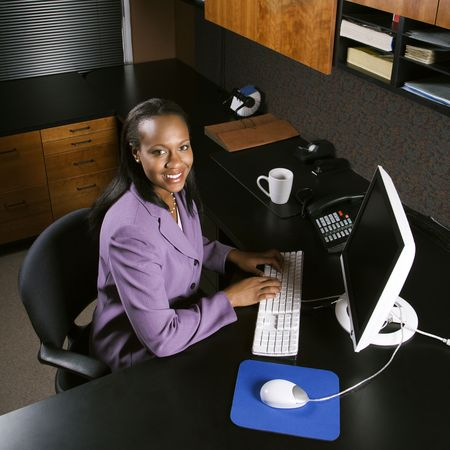 High angle view of African-American young adult business woman working at computer in office smiling and looking at viewer. Stock Photo - 1795607