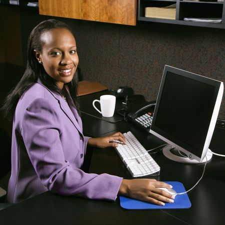 African-American young adult business woman working at computer in office smiling and looking at viewer.