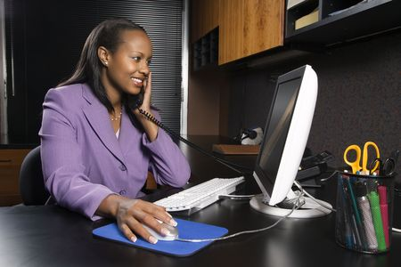 African-American young adult smiling business woman talking on phone and working at computer in office.