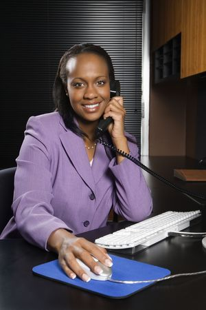 African-American young adult business woman talking on phone and working at computer in office smiling and looking at viewer. photo