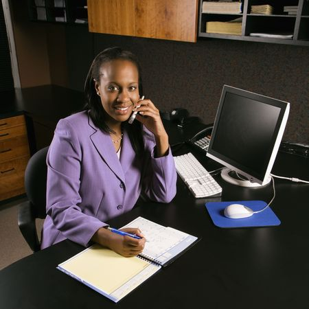 African-American young adult business woman talking on cell phone and writing in planner in office smiling and looking at viewer. Stock Photo - 1796916