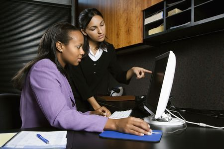 African-American and Indian young adult business women looking and pointing at computer in office. Stock Photo - 1796927