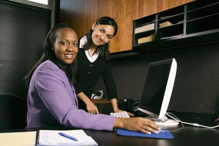 African-American and Indian young adult business women working at computer in office smiling and looking at viewer. photo