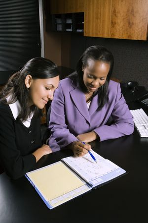 African-American and Indian young adult business women working together in office. photo