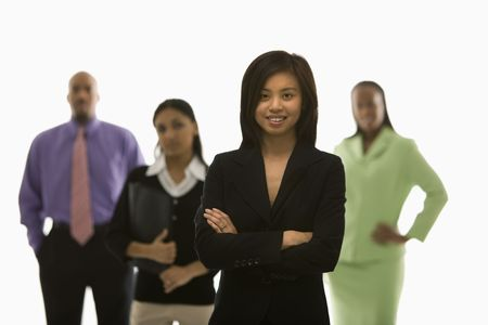 Portrait of Vietnamese businesswoman smiling with arms crossed with others in background. Stock Photo - 1796804