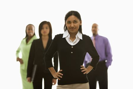 Portrait of Indian businesswoman smiling with hands on hips with others in background. Stock Photo - 1796829