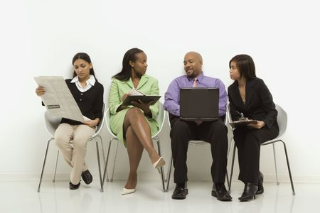 Multi-ethnic business group of men and women sitting looking at laptop and papers. Stock Photo - 1796834