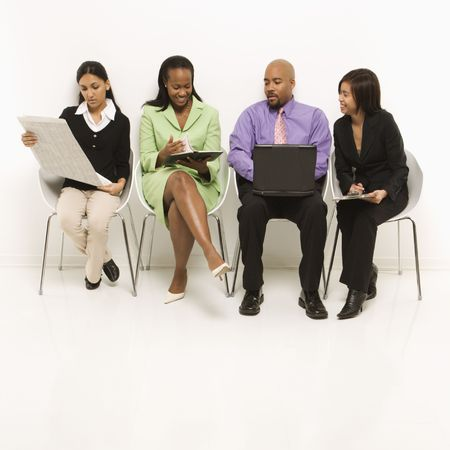 Multi-ethnic business group of men and women sitting looking at laptop and papers. Stock Photo - 1796833