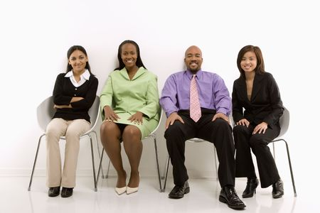 Multi-ethnic business group of men and women sitting and smiling at viewer. Stock Photo - 1796841