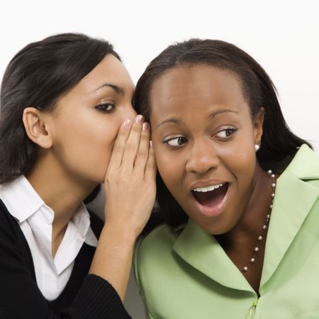 Indian young adult woman whispering in ear of mid-adult African-American woman. Stock Photo - 1796987