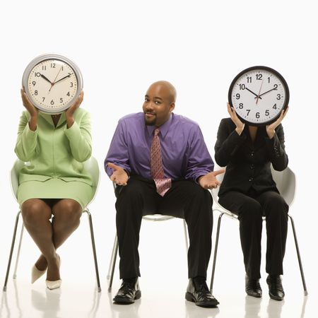Businesswomen sitting holding clocks over faces while African-American businessman shrugs. Stock Photo - 1795511