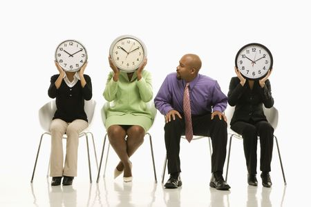 conceal: Businesswomen sitting holding clocks over faces while African-American businessman looks on. Stock Photo