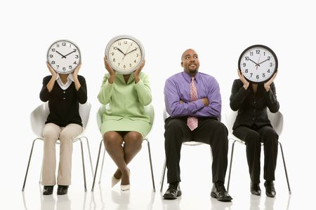 Businesswomen sitting holding clocks over faces while African-American businessman looks on. Stock Photo - 1796836
