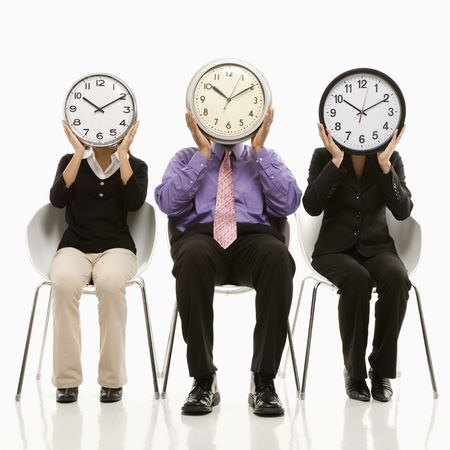 Multi-ethnic business people sitting holding clocks over faces.