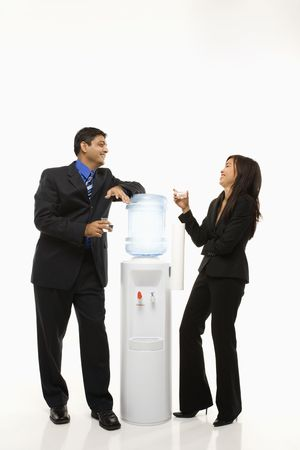 Vietnamese businesswoman and Indian businessman conversing at water cooler. Stock Photo - 1796794