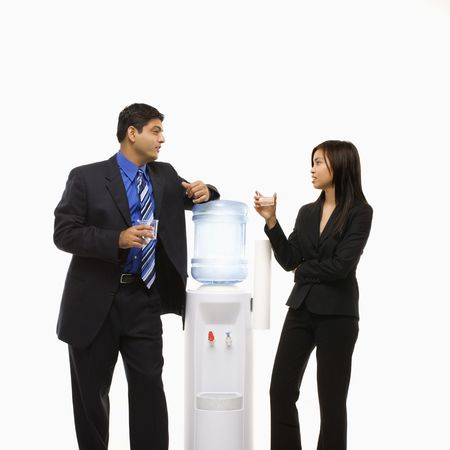 man drinking water: Vietnamese businesswoman and Indian businessman conversing at water cooler.