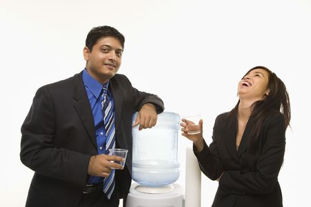 Laughing Vietnamese businesswoman standing at water cooler with Indian businessman. photo