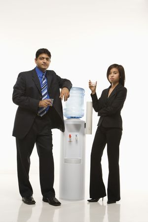 Vietnamese businesswoman and Indian standing at water cooler looking at viewer. photo