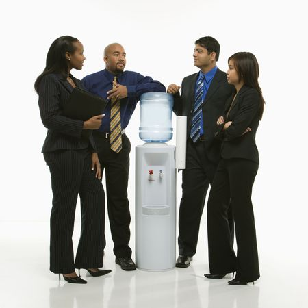 Multi-ethnic business group of men and women standing at water cooler conversing. Stock Photo