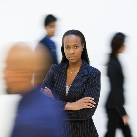 African-American businesswoman standing with arms crossed while others walk by. photo