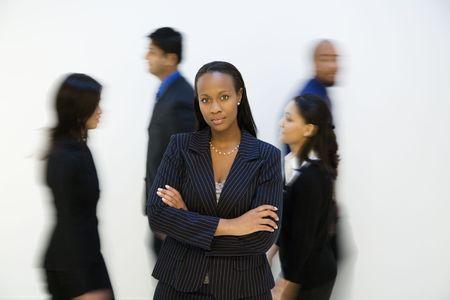 one person with others: African-American businesswoman standing with arms crossed while others walk by.