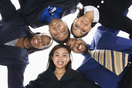 Low angle portrait  of multi-ethnic business group of men and women in huddle looking at viewer. photo