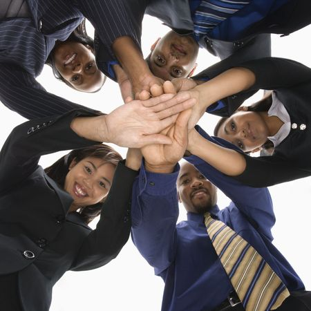 Low angle portrait of multi-ethnic business group of men and women with hands in huddle.