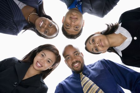 huddle: Low angle portrait  of multi-ethnic business group of men and women in huddle looking at viewer. Stock Photo