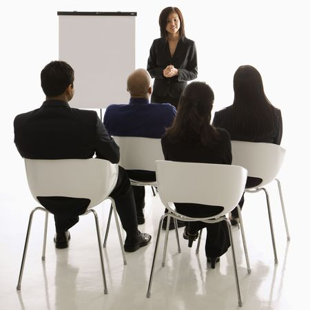 one person with others: Vietnamese mid-adult woman standing in front of business group leading presentation. Stock Photo
