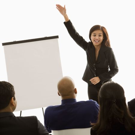 Vietnamese mid-adult woman standing in front of business group gesturing for a presentation. photo