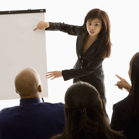Vietnamese mid-adult woman standing in front of business group pointing to presentation. Stock Photo - 1796839