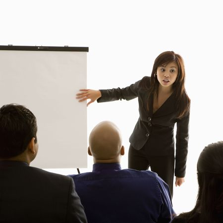 Vietnamese mid-adult woman standing in front of business group pointing to presentation. photo