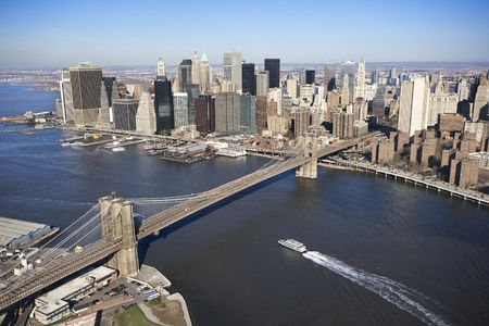 aerial photograph: Aerial view of in New York City with  Brooklyn Bridge and Manhattan skyline with ferry boat.