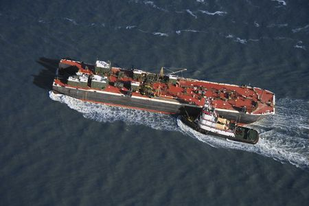 Aerial view of tugboat pushing tanker. Stock Photo