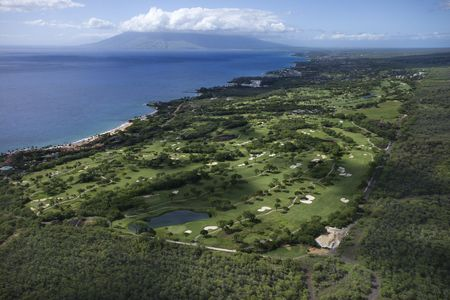 Aerial of golf course on Maui, Hawaii coastline with Pacific ocean.
