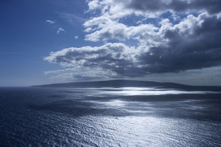 Island in Pacific ocean with puffy clouds. Stock Photo