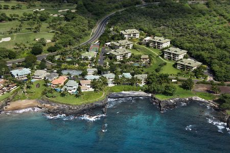 clustered: Aerial of houses clustered by Maui, Hawaii coast.