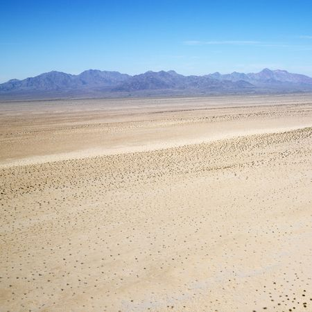 Aerial view of remote California desert with mountain range in background. photo