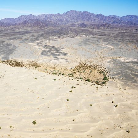 torrid: Aerial view of remote California desert with mountain range in background.