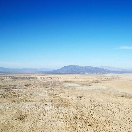 aerial photograph: Aerial view of remote California desert with mountain range in background.
