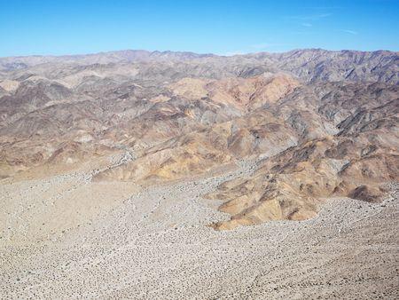 torrid: Aerial veiw of remote California desert with mountain range in background.