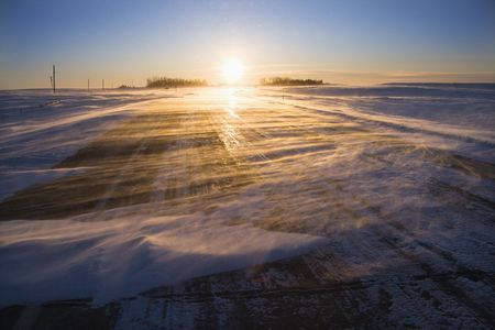 blustery: Ice covered road with sun rising in distance. Stock Photo
