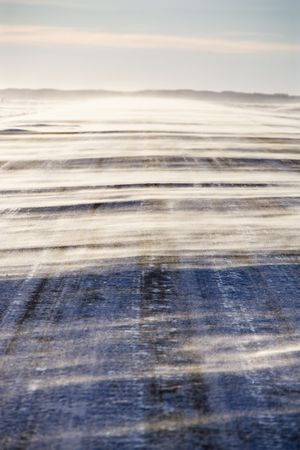 blustery: Ice covered road with snow being blown over. Stock Photo