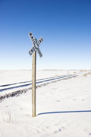 Railroad crossing sign by tracks in rural desolate snowy landscape. photo