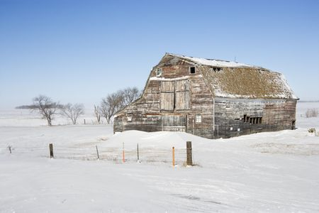 Rustic barn in rural snow covered landscape. photo
